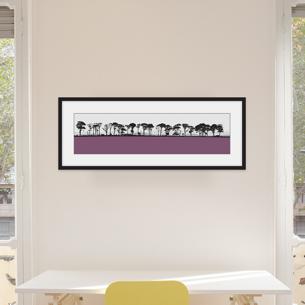 Art print of Northumberland countryside by designer Jacky Al-Samarraie, mounted and framed on a wall in an office room. The print colour is pink.