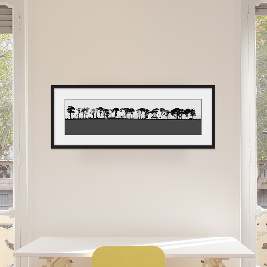 Art print of Northumberland countryside by designer Jacky Al-Samarraie, mounted and framed on a wall in an office room. The print colour is grey.