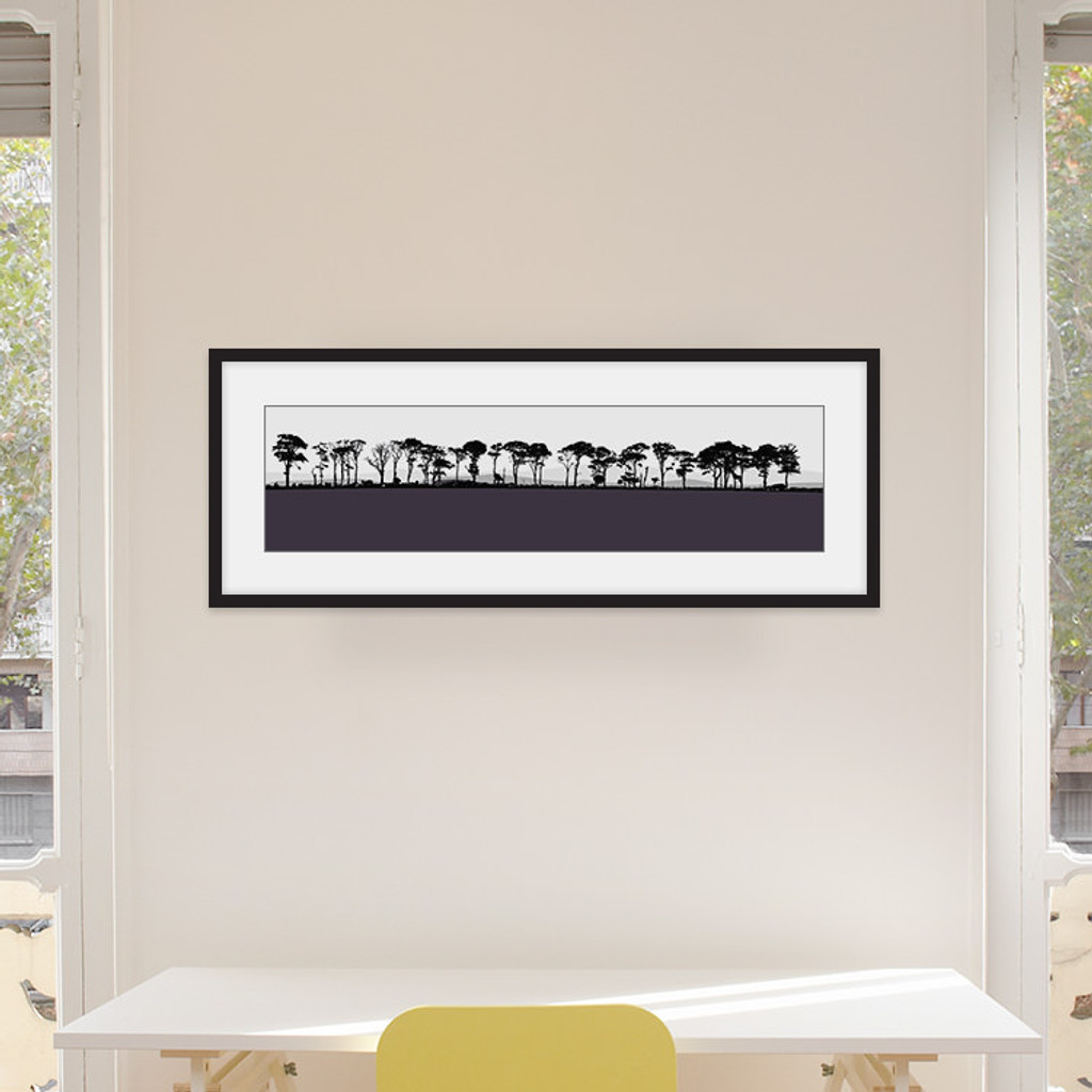 Art print of Northumberland countryside by designer Jacky Al-Samarraie, mounted and framed on a wall in an office room. The print colour is aubergine.