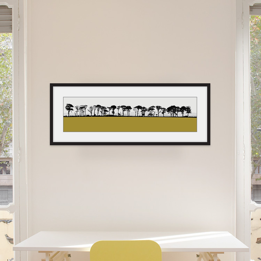 Art print of Northumberland countryside by designer Jacky Al-Samarraie, mounted and framed on a wall in an office room. The print colour is mustard.
