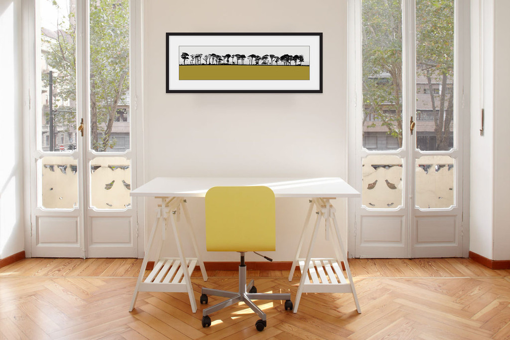 Landscape print of Northumberland countryside by designer Jacky Al-Samarraie, mounted and framed on a wall in an office room. The print colour is mustard.