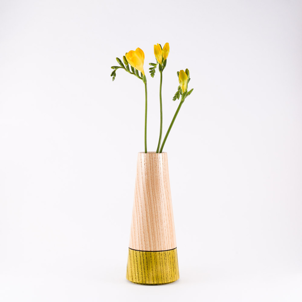 Green wood stem vase by designer Jacky Al-Samarraie, with flowers in glass tube