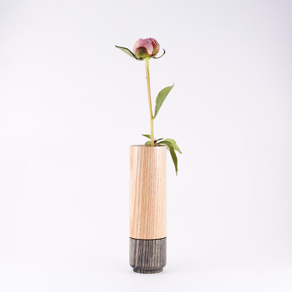 Grey wood stem vase by designer Jacky Al-Samarraie, with flowers in glass tube