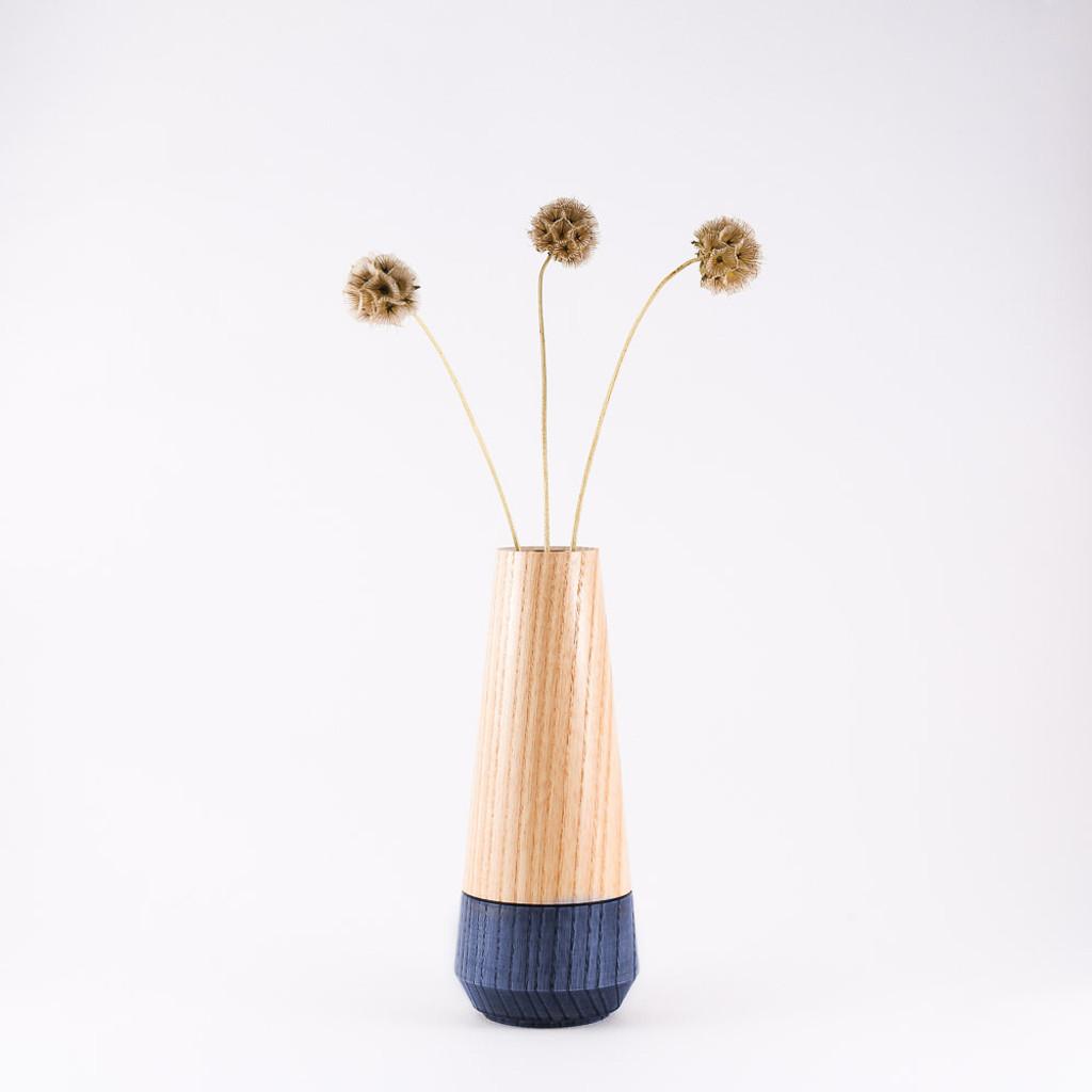 Blue wood stem vase by designer Jacky Al-Samarraie, with flowers in glass tube