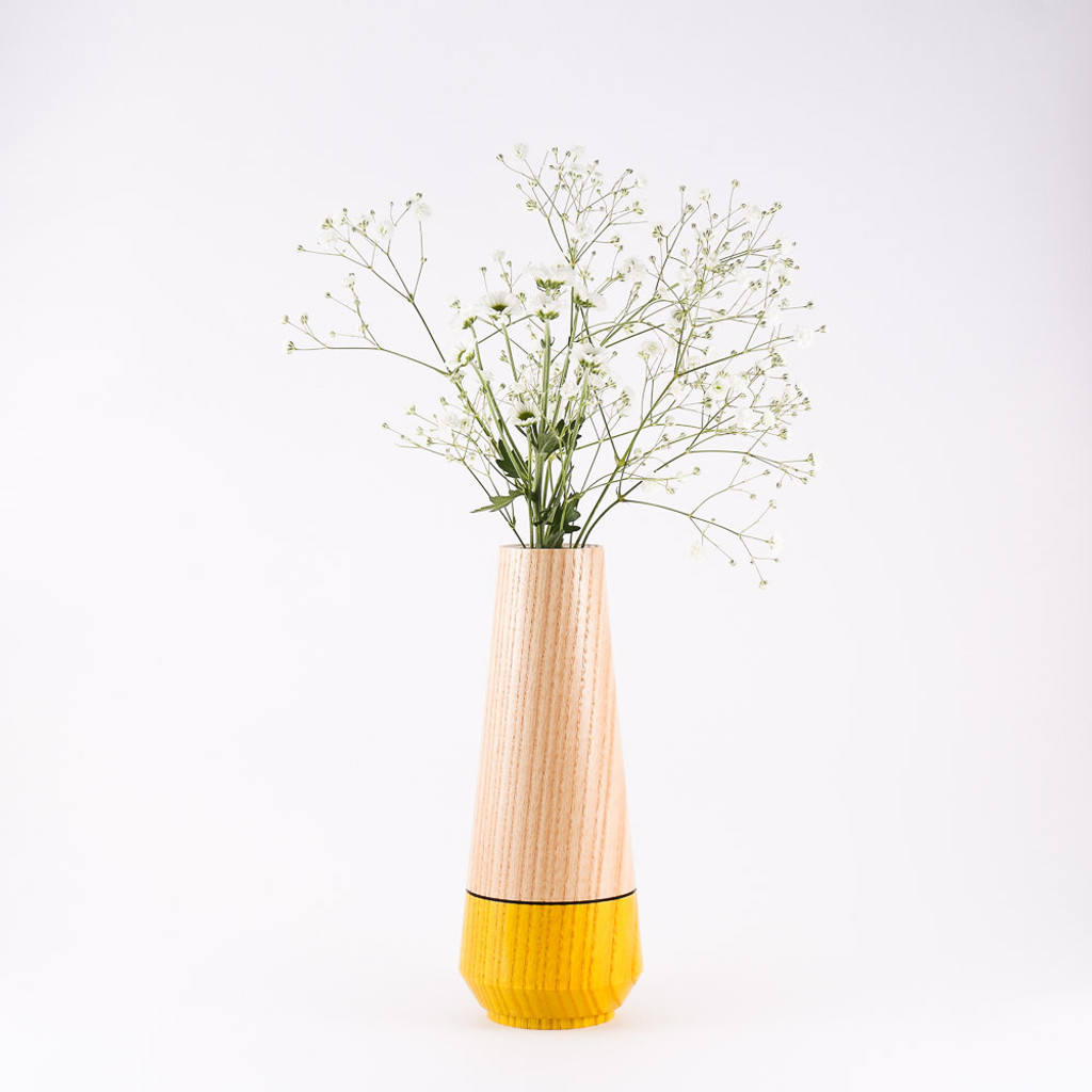 Yellow wood stem vase by designer Jacky Al-Samarraie, with flowers in glass tube