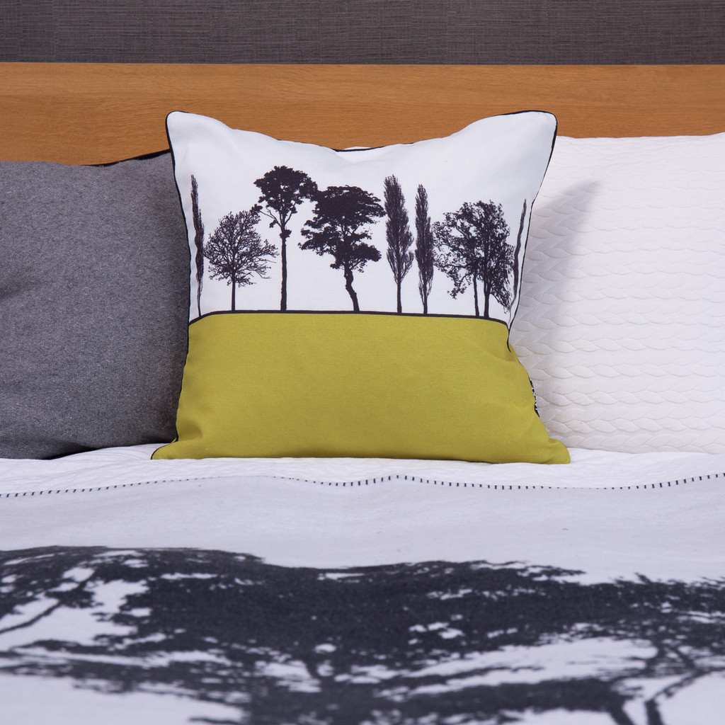 Mustard English countryside landscape cushion shown on bed, by designer Jacky Al-Samarraie