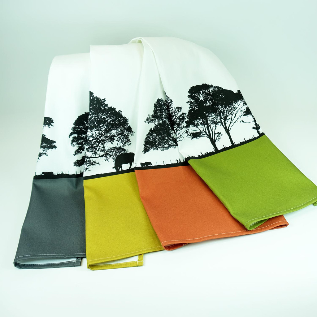 Set of four brightly coloured cotton tea towels with a landscape tree design, The Art Rooms