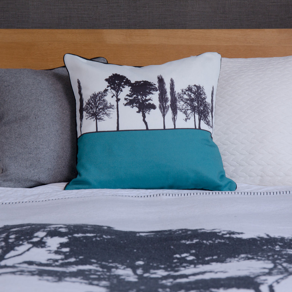 Teal English countryside landscape cushion shown on bed, by designer Jacky Al-Samarraie