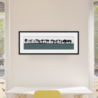 Art print of Northumberland countryside by designer Jacky Al-Samarraie, mounted and framed on a wall in an office room. The print colour is slate.