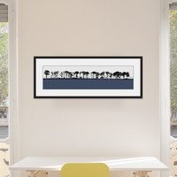 Art print of Northumberland countryside by designer Jacky Al-Samarraie, mounted and framed on a wall in an office room. The print colour is blue.