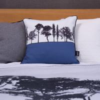 Blue English countryside landscape cushion shown on bed, by designer Jacky Al-Samarraie