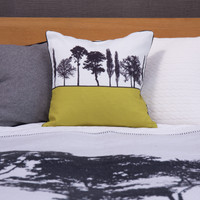 Mustard Engligh countryside landscape cushion shown on bed, by designer Jacky Al-Samarraie