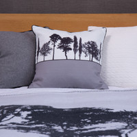 Grey Engligh countryside landscape cushion shown on bed, by designer Jacky Al-Samarraie