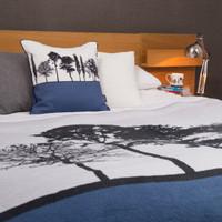 Blue woven cotton landscape throw blanket on bed by designer Jacky Al-Samarraie
