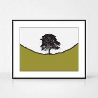 Landscape print of Sycamore Gap along Hadrian's Wall in Northumberland by designer Jacky Al-Samarraie.  Shown in frame for reference.