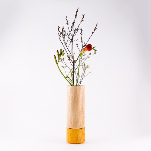 Orange wood stem vase by designer Jacky Al-Samarraie, with flowers in glass tube