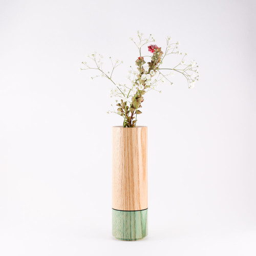 Turquoise wood stem vase by designer Jacky Al-Samarraie, with flowers in glass tube