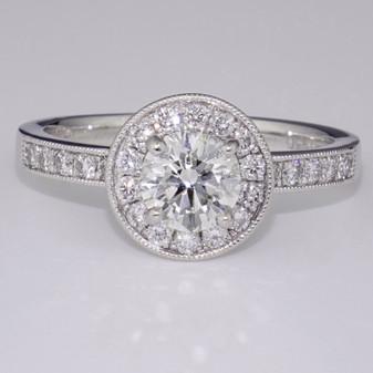 Platinum diamond halo ring with milgrain edge and diamond shoulders