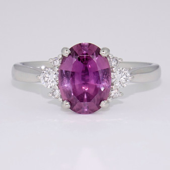 Platinum oval cut raspberry sapphire and round brilliant cut diamond ring