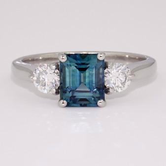 Platinum emerald cut teal sapphire and round brilliant cut diamond ring