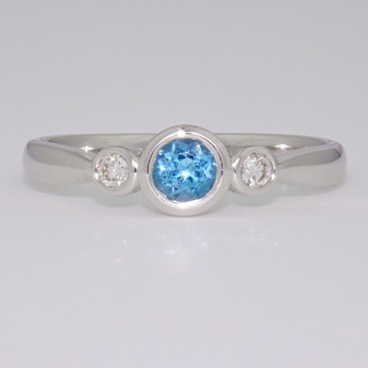 9ct white gold round cut blue topaz and diamond rubover ring