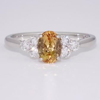 Platinum oval cut Imperial topaz and round brilliant cut diamond ring