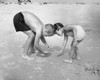 Boy with his sister collecting stones on the beach Poster Print - Item # VARSAL25516729