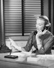 Businesswoman talking on the telephone and reading a document in an office Poster Print - Item # VARSAL25535402