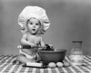 1960s Baby Seated On Checkered Tablecloth Wearing Chef'S Hat Mixing Eggs Milk And Flour In Large Bowl Looking At Camera - Item # VARPPI177098