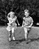 1930s-1940s Smiling Boy And Girl Running In Summer Backyard Grass Looking At Camera Print By Vintage Collection - Item # PPI177417LARGE