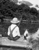 1920s-1930s Farm Boy Wearing Straw Hat And Overalls Sitting On Log With Spotted Dog Fishing In Pond Print By Vintage - Item # VARPPI172398