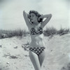 1950s Brunette Bathing Beauty In Polka Dot Bikini Standing In Sand With Hands Behind Head Looking At Camera Print By - Item # PPI177346LARGE