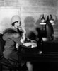1920s Smiling Woman With Pen To Lips Wearing Cloche Hat And Fur Collar Coat Writing A Letter At Hotel Lobby Desk With - Item # PPI177405LARGE