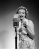 1950s Portrait Woman Entertainer Singing Into A Microphone Studio Looking At Camera Print By Vintage Collection - Item # VARPPI178990