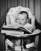 Baby sitting in a high chair and looking at a book Poster Print - Item # VARSAL2559707