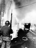 National Guard In Watts During The 1965 Race Riot. Debris Litters The Streets And A Geyser From Broken Fire Hydrant Sprays At Left. August 14 History - Item # VAREVCCSUA001CS688