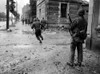 U.S. Soldiers Moving Through The Streets Of Cherbourg. One By One They Dash Across A Street To Evade German Sniper Fire. June 22-25 History - Item # VAREVCHISL037EC229