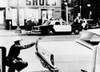 1965 Watts Riots. A Policeman Aims His Revolver At Building Where A Sniper Shot At Passing Cars. Across The Street History - Item # VAREVCCSUA001CS694