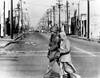 Peace In The Midst Of Riot. A National Guardsman Escorts An Elderly African American Woman Resident Of The Riot Area Across Fire And Violence-Scarred Street Of Watts. Aug. 15 History - Item # VAREVCCSUA001CS692