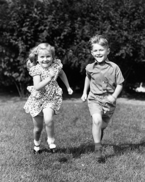 1930s-1940s Smiling Boy And Girl Running In Summer Backyard Grass Looking At Camera Print By Vintage Collection - Item # VARPPI177417