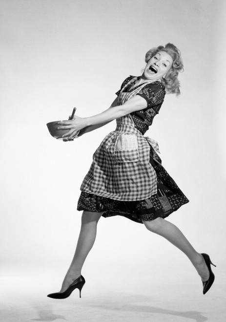 1960s Laughing Blonde Woman In Checkered Apron Jumping With Glee Holding Spoon Mixing Bowl With Both Hands Looking At - Item # VARPPI179117