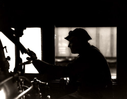 1920s-1930s-1940s Silhouetted Train Engineer At Controls In Locomotive Cab Of Railroad Steam Engine Hand On Throttle - Item # PPI179043LARGE