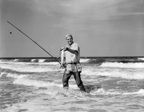 1950s Older Man Standing In Surf In Waders Holding Fish In One Hand Fishing Pole In Other Print By Vintage Collection - Item # PPI176481LARGE