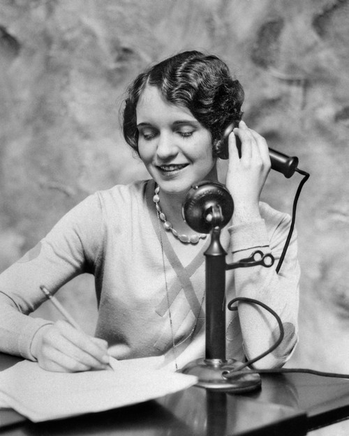 1920s Smiling Woman Sitting At Desk Writing And Talking On Candlestick Telephone Print By Vintage Collection - Item # PPI177676LARGE