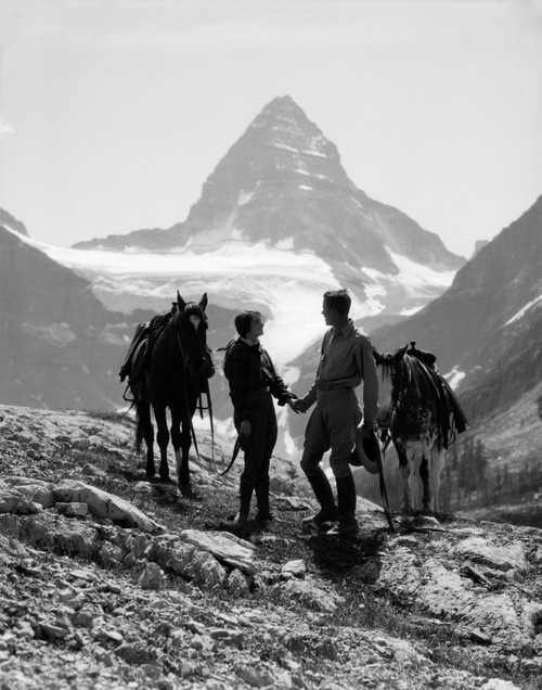 1920s-1930s Couple Man Woman Silhouetted Holding Hands Standing With Horses In Mountains Western Mt. Assiniboine Canada - Item # VARPPI177645