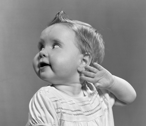 1940s-1950s Close-Up Portrait Of Baby Girl With Curl On Top Of Head Looking To Side With Hand Held Up Beside Ear Print - Item # PPI177161LARGE