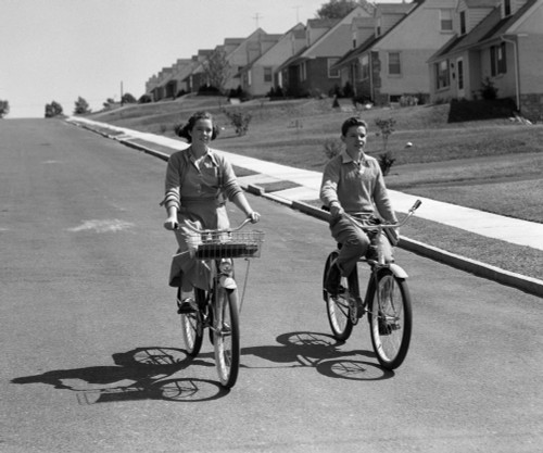1950s Teen Boy Girl Couple Riding Bikes Down Residential Street Poster Print By Vintage Collection - Item # VARPPI177175