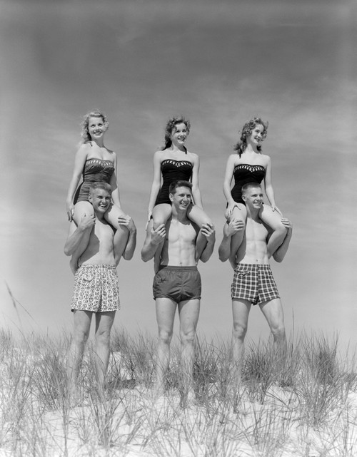 1950s-1960s Three Couples At Beach On Dunes With Women In Identical Bathing Suits Sitting On Men'S Shoulders Print By - Item # PPI172405LARGE