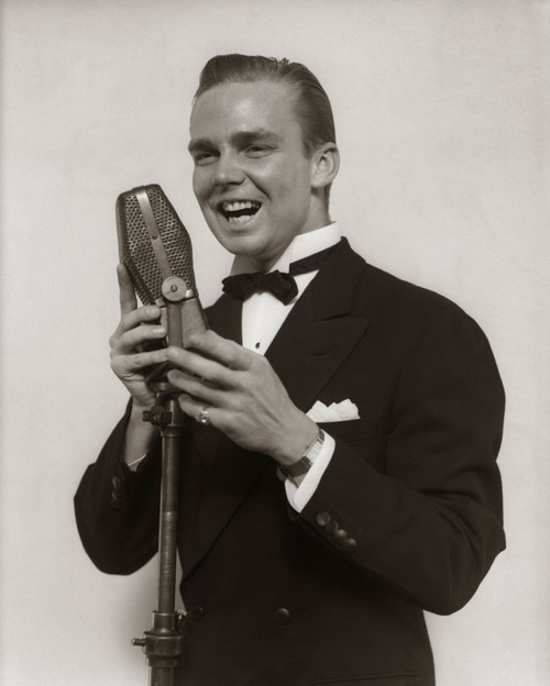 1920s-1930s Smiling Man Radio Singer Entertainer Crooner In Tuxedo Singing Into Microphone Print By Vintage Collection - Item # PPI178704LARGE