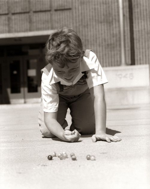 1950s Smiling Boy Ready To Shoot Kneeling On School Yard Ground Playing Game Of Marbles Print By Vintage Collection - Item # VARPPI177188